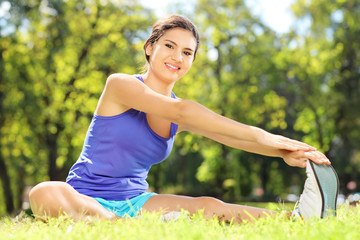 Young female athlete on excercising mat and stretching in a park