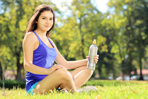 Young female athlete on grass after exericise and holding bottle