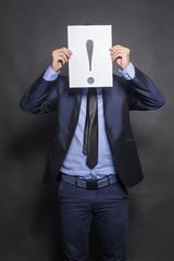 Businessman holding exclamation mark