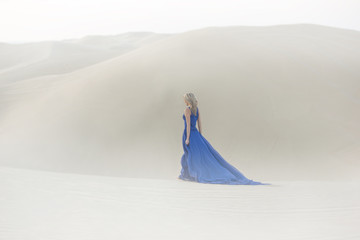 Beautiful young woman walks in desert, long, blue dress