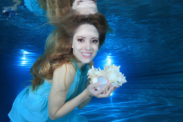Woman underwater in the pool with sea shell