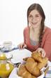 Junge Frau beim Frühstück - Croissant nehmen