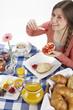 Junge Frau beim Frühstück - Brötchen mit Marmelade