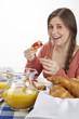 Junge Frau beim Frühstück - Brötchen mit Marmelade essen