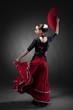young woman dancing flamenco with fan on black