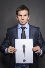 Businessman holding exclamation mark