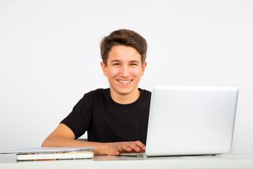 Junger Mann lacht beim Lernen am Notebook