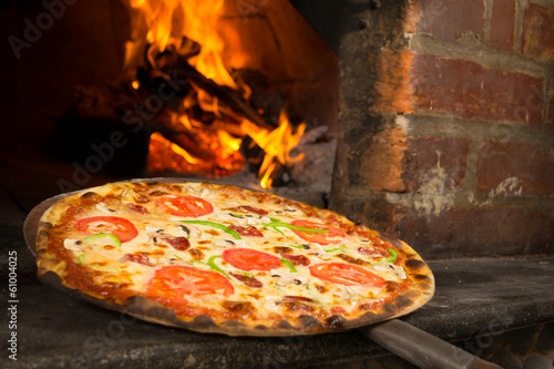 Foto op Canvas Pizzeria Pizza entering a wood oven