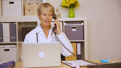 Doctor working in office and getting phone call