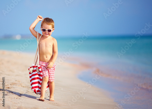 happy kid boy walking the summer beach