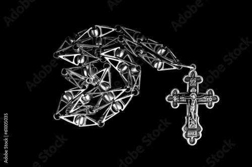 Silver chain with Russian Orthodox cross on black background.