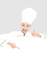 young woman chef smiling and thumb up   with blank board