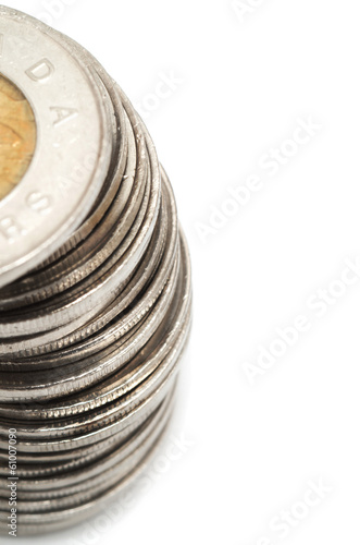 Canadian dollar coins stacked on white background