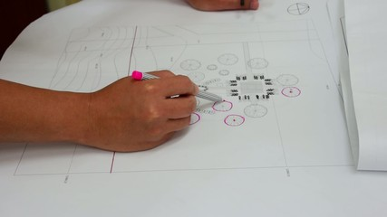 Architect is circling a tree symbol on a blueprint of garden