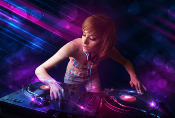 Young DJ playing on turntables with color light effects