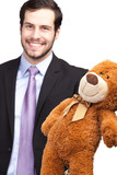 smiling businessman giving a teddy bear