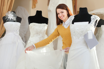 bride chooses wedding gown at bridal boutique