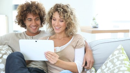 Cheerful couple having fun using tablet in sofa