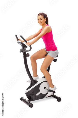 Young woman uses stationary bicycle trainer.