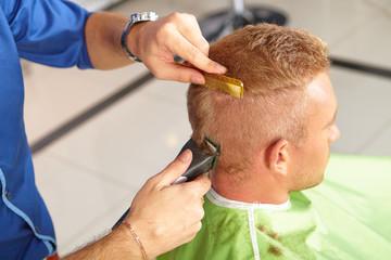 Hair salon. Hairdresser does haircut for man.