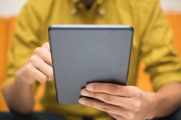 Close-up image of a man using a digital tablet