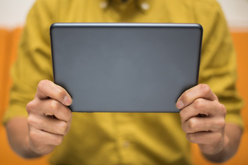 Close-up image of a man holding a digital tablet