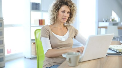 Smiling woman sitting in front of laptop computer