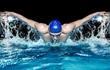 Leinwandbild Motiv Muscular young man in blue cap in swimming pool