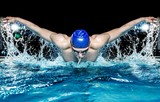 Fototapety Muscular young man in blue cap in swimming pool