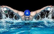 Muskuläre junger Mann in blauer Kappe im Schwimmbad