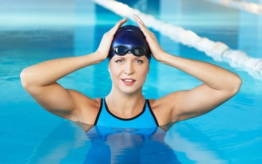 Young woman wearing blue swimming suit and hat in swimming pool