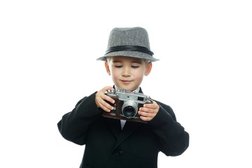 Little boy in hat and black suit with vintage camera