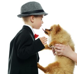 Little boy in hat and black suit with little spitz