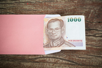 A one thoundsand Thai banknote in the envelope