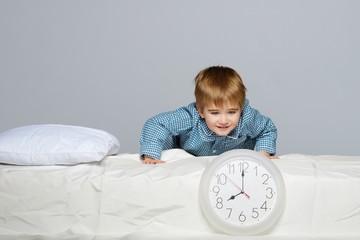 Little boy in blue pyjamas with clock