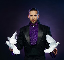Young handsome brunette magician man in stage costume