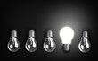 Idea concept with row of light bulbs, one of them is glowing.