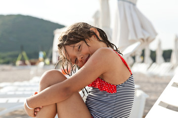 little girl sitting on a deck chair at the beach