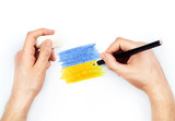 Man's hands with pencil draws flag of Ukraine on white
