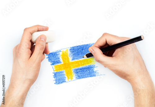 Man's hands with pencil draws flag of Sweden on white