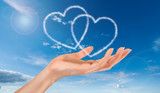 woman hand and heart shaped clouds on blue sky background