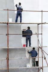 Workers at scaffolding spreading stucco over mortar, styrofoam