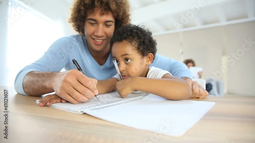 Daddy and son drawing on notebook at home