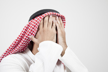 arab man covering his face
