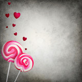 Two colorful lollipops with floating hearts on grunge background