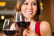 Chinese woman toasting in  restaurant with red wine