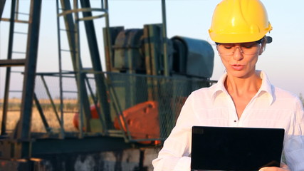 Smiling female engineer in an oilfield working with notebook