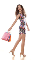 beautiful and smiling teenage girl holding shopping bags