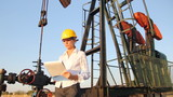 Business woman writing on clipboard in an oil field