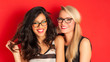 Blonde and brunette women having fun portrait against red backgr